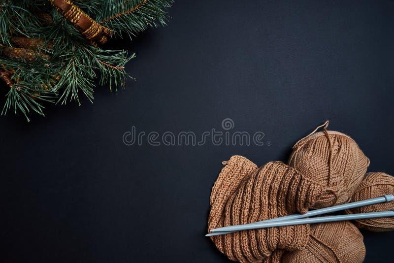 毛线、编织针和篮子与杉木分支在黑暗的背景 免版税图库摄影
