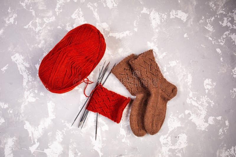 毛线、编织针和被编织的袜子球在灰色水泥背景 库存图片