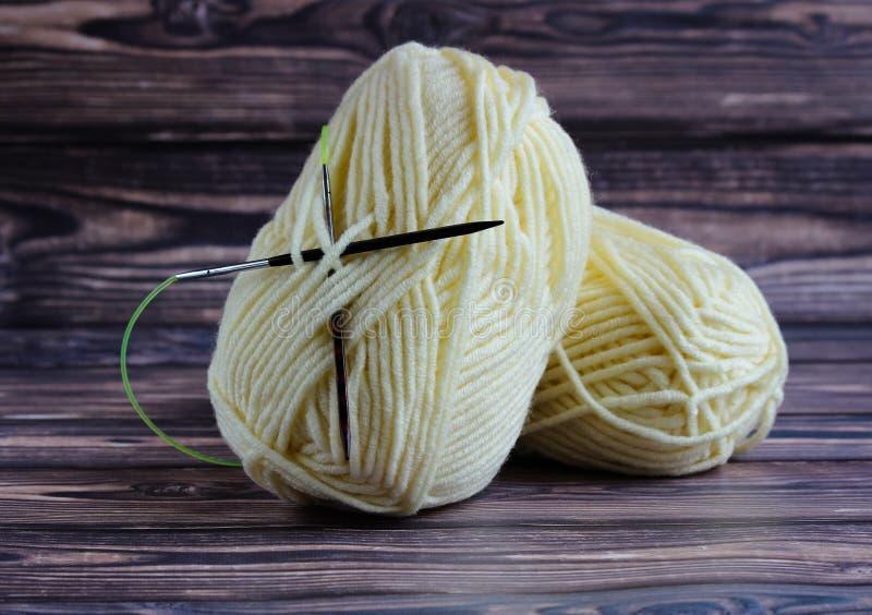 毛线两个球编织的谎言的在与编织针的黑暗的背景 库存图片