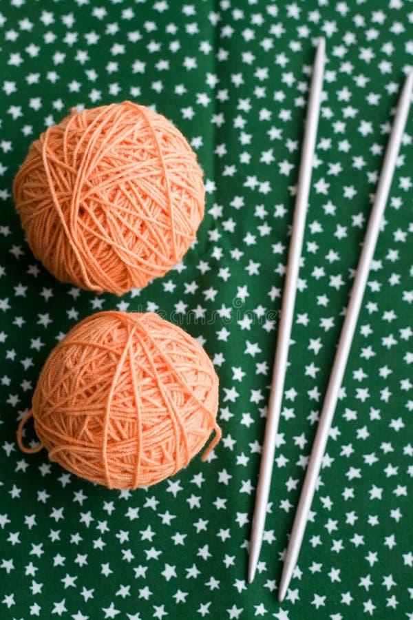 毛线和编织针橙色钩针编织两个球  图库摄影
