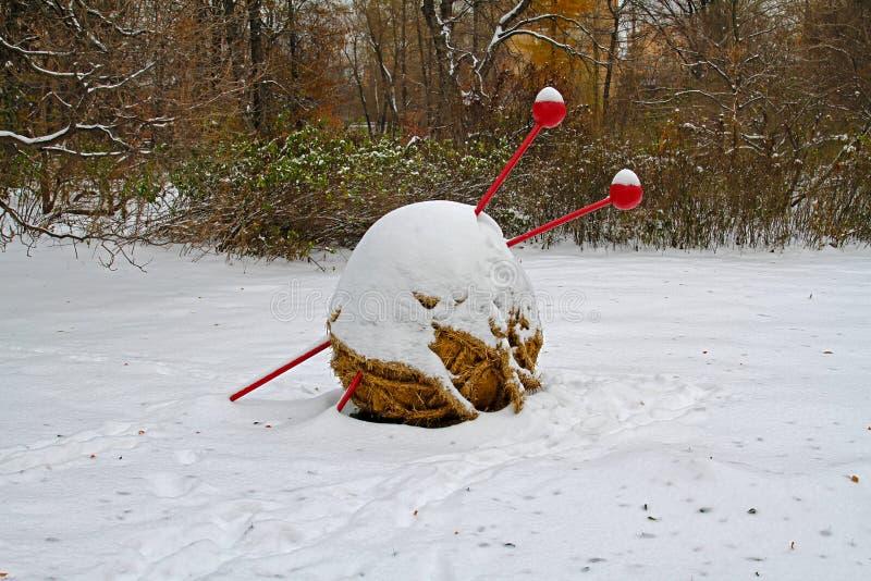毛线和编织针秸杆球在雪下 免版税库存图片