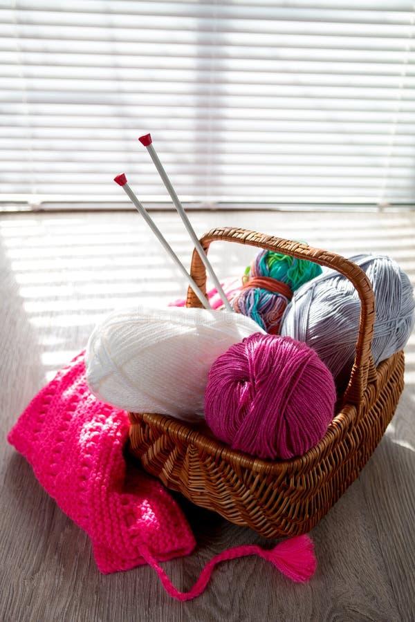 毛线球和在篮子的编织针在与窗口的一张木灰色桌上点燃 关闭 手工制造 免版税库存图片