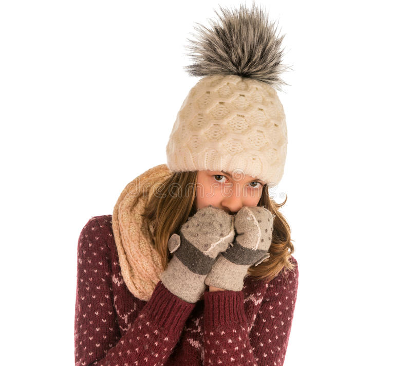 毛线衣、帽子、围巾和手套的逗人喜爱的女孩盖了她的面孔 免版税库存照片