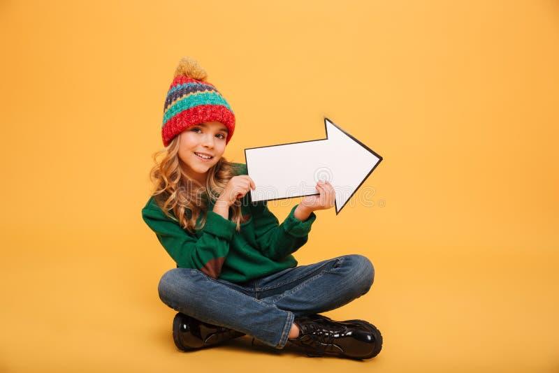 毛线衣和帽子的喜悦的女孩坐地板 库存图片