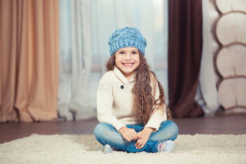 毛线衣和帽子的小女孩坐地板在一个木房子,圣诞节里 库存照片