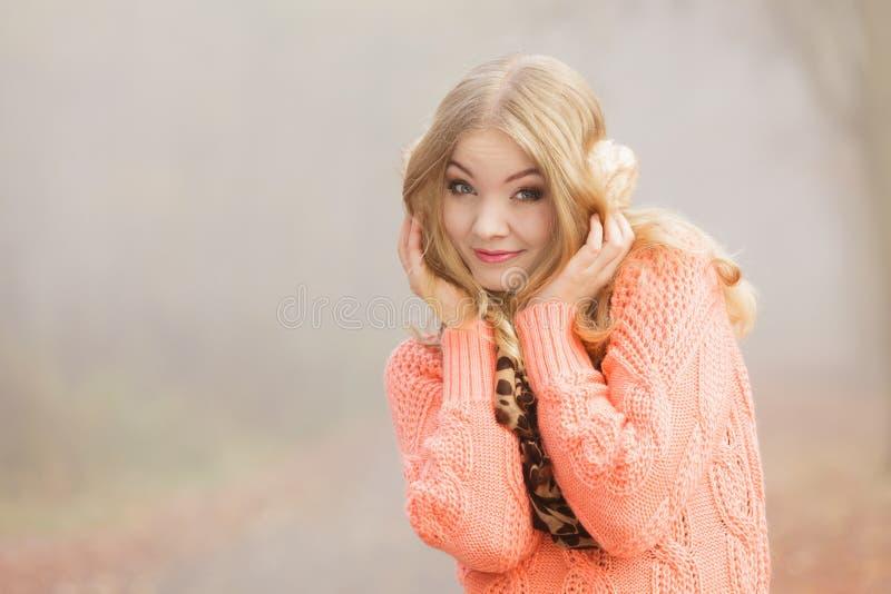 毛线衣和御寒耳罩的微笑的时尚妇女 免版税库存图片
