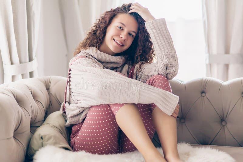 毛线衣和连衫裤的十几岁的女孩在长沙发 免版税库存照片