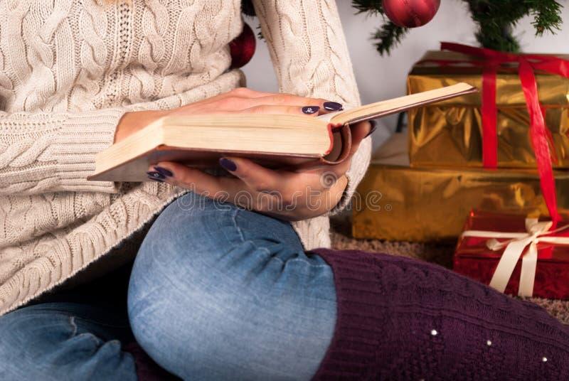 毛线衣的女孩在手和圣诞树上在背景中的拿着书和礼物盒 图库摄影