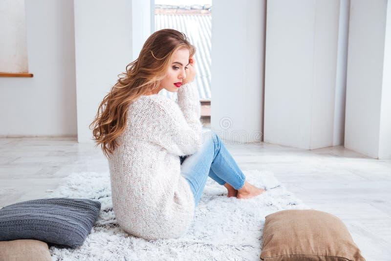 毛线衣的妇女坐地毯和饮用的茶 库存照片