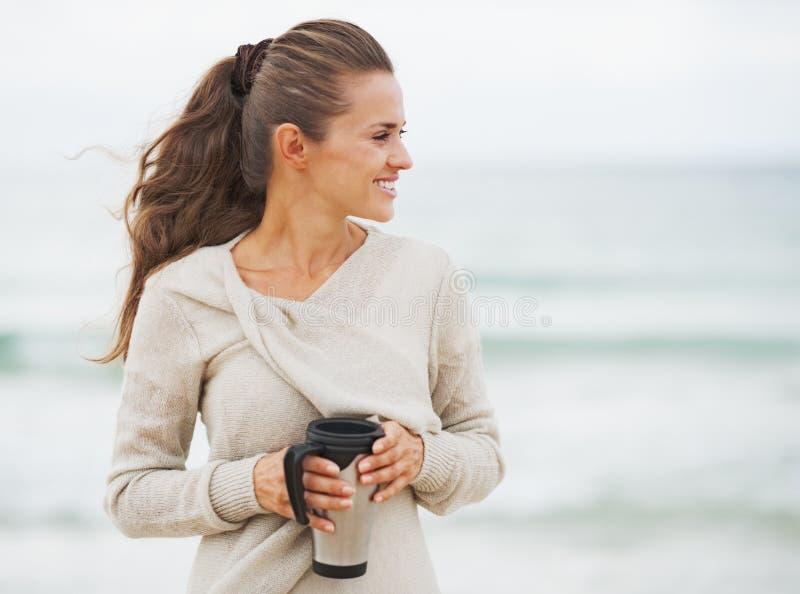 毛线衣的愉快的少妇在与杯子的海滩热的饮料 库存照片