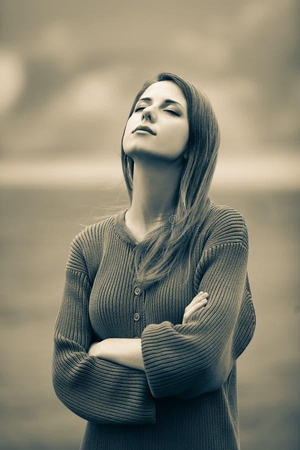毛线衣的美丽的成人女孩在麦田 免版税库存照片