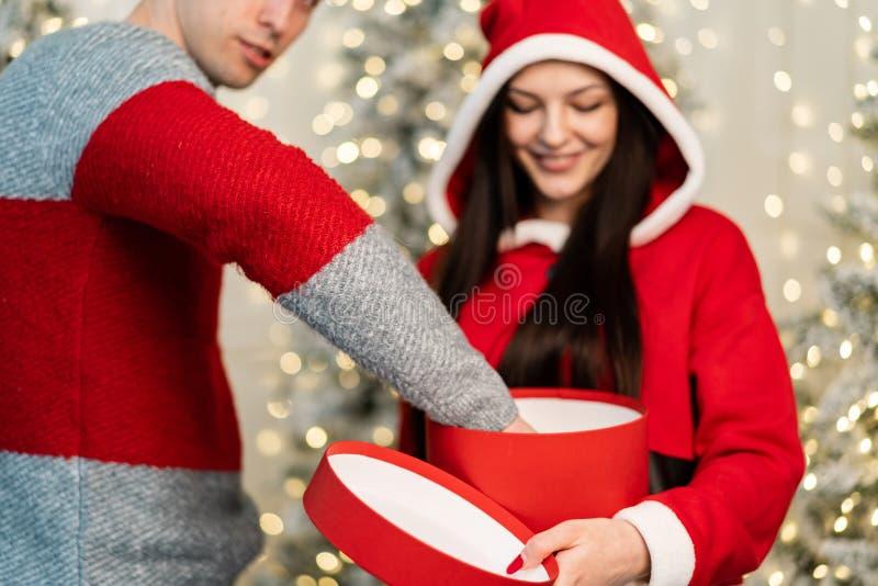 毛线衣藏品礼物的年轻美女在手和帅哥上从箱子里面拉礼物 免版税图库摄影