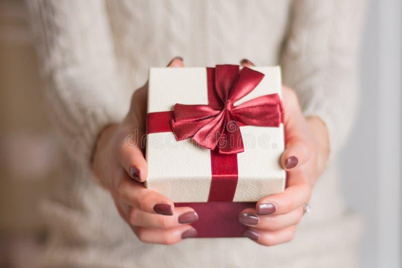 毛线衣藏品礼物盒的女孩有红色丝带领带弓的 免版税图库摄影