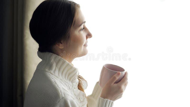 毛线衣饮用的咖啡的年轻美丽的深色的妇女在窗口附近的 免版税图库摄影
