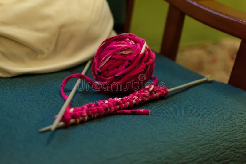 毛线钩针编织和丝球在沙发的 库存照片