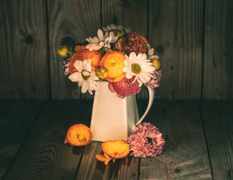 毛茛五颜六色的花束在一个白色水罐的 免版税库存照片