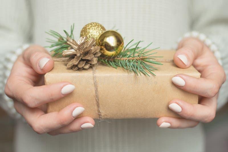 毛衣的一个女孩拿着一个礼物 冬天礼物、圣诞节和新年设计的布局  图库摄影