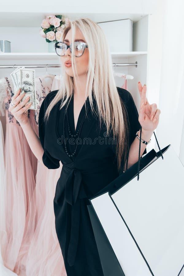 毫华女孩金钱购物的高价衣服 免版税库存照片