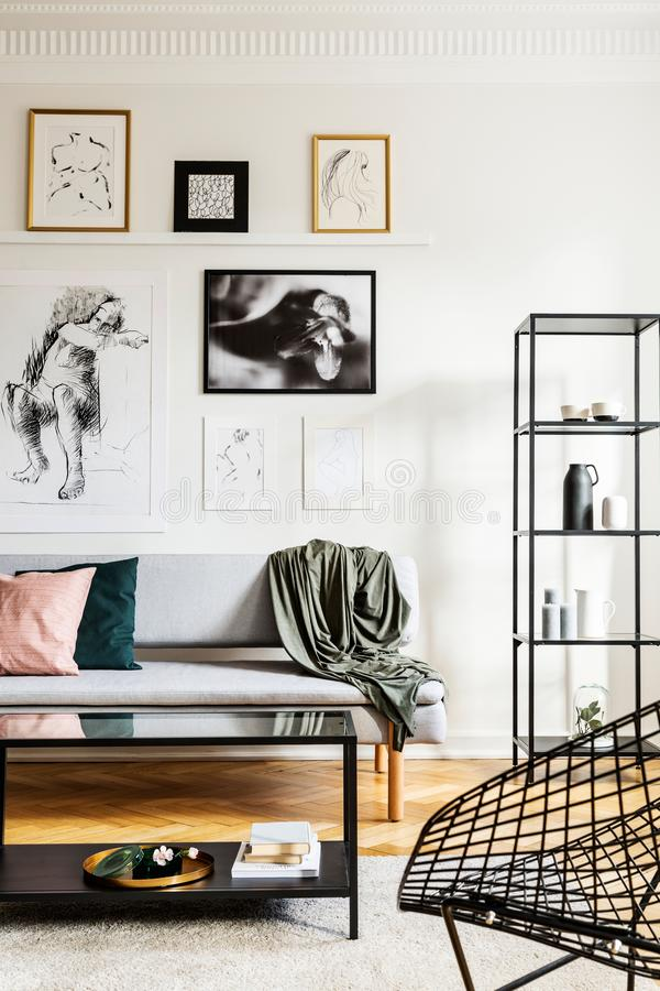 毯子和枕头在沙发在明亮的客厅有海报画廊的在墙壁上 免版税库存图片