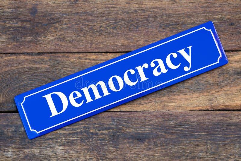 民主在木背景的路牌 库存图片