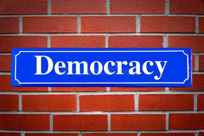 民主在砖墙上的路牌 库存图片