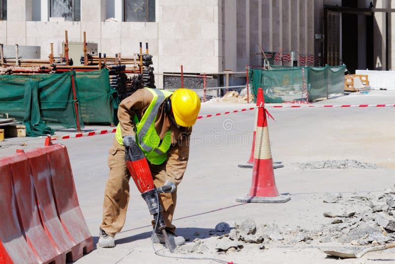 民工使用一台手提凿岩机破坏一个混凝土路面 免版税库存照片
