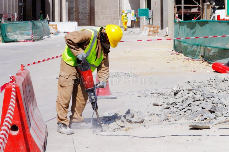 民工使用一台手提凿岩机破坏一个混凝土路面 免版税库存图片