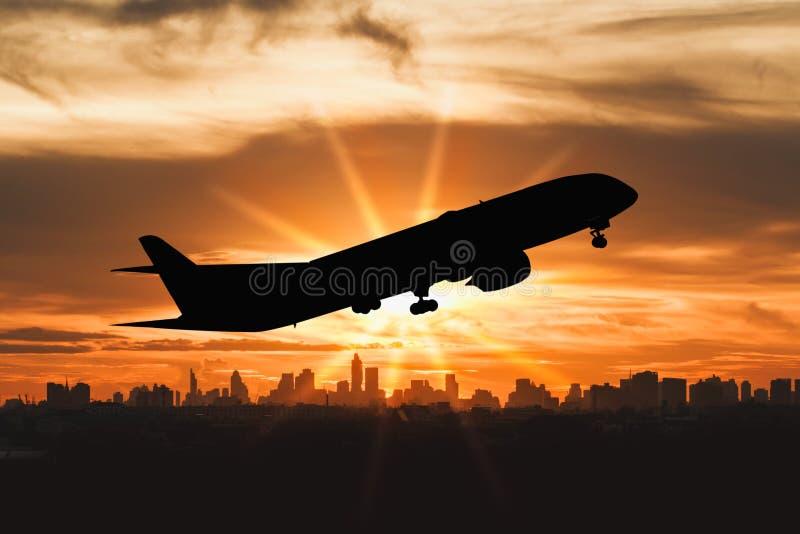 民航飞机飞行剪影在城市的 免版税库存照片
