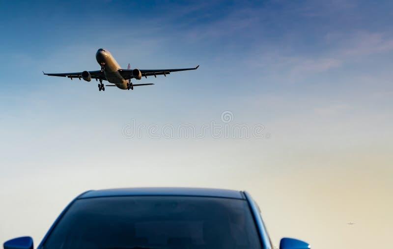 民航 客机接进着陆蓝色SUV汽车在有天空蔚蓝和云彩的机场在日落 到来飞行 图库摄影