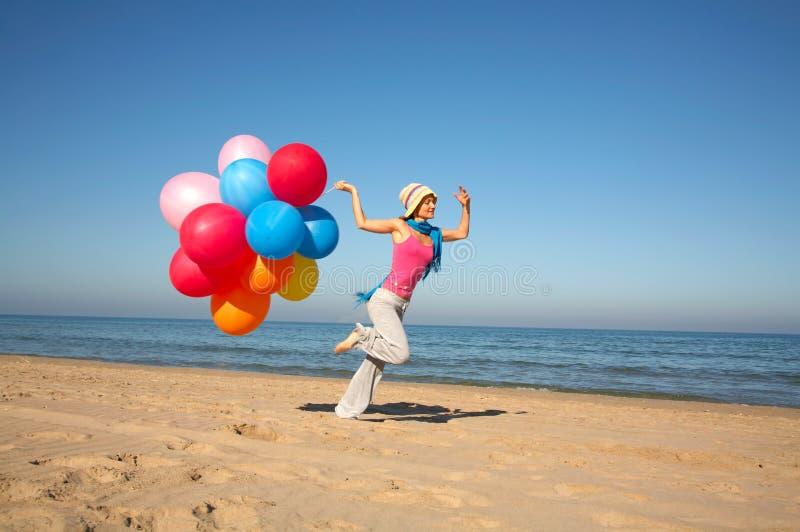 气球使连续妇女年轻人靠岸 免版税库存照片