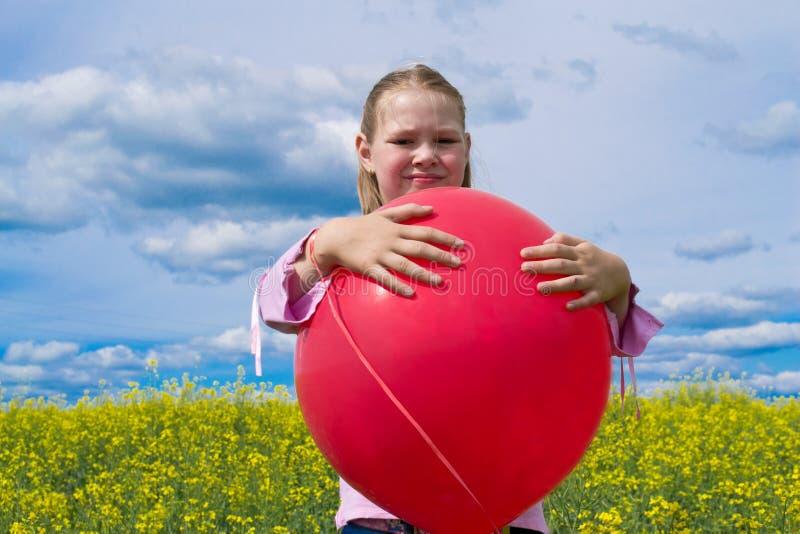 气球女孩草甸红色 免版税图库摄影