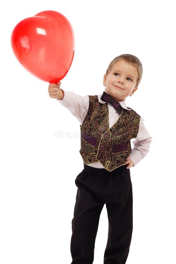 气球男孩产生少许红色微笑 库存照片