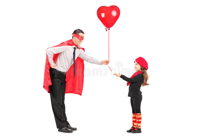 给气球的男性超级英雄一个小女孩 库存照片