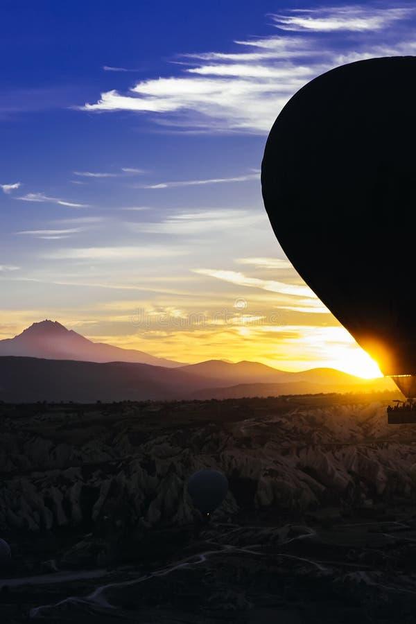 气球的飞行的垂直的照片在山的在黎明在土耳其 免版税库存照片