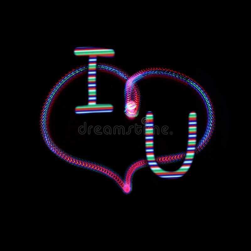 氖发光的心脏和在上写字I和U 图库摄影