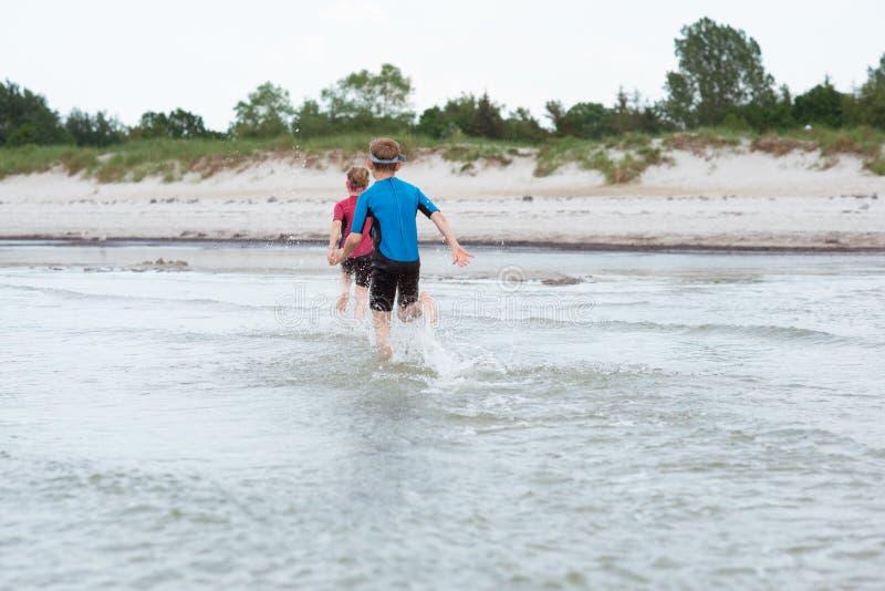 氯丁胶swimingsuit playin和赛跑的两个愉快的兄弟姐妹孩子在海 库存图片