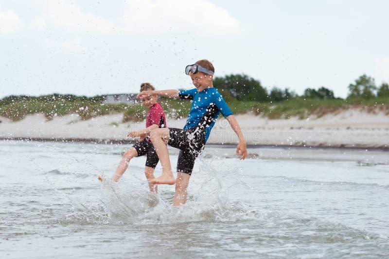 氯丁胶swimingsuit playin和赛跑的两个愉快的兄弟姐妹孩子在海 图库摄影