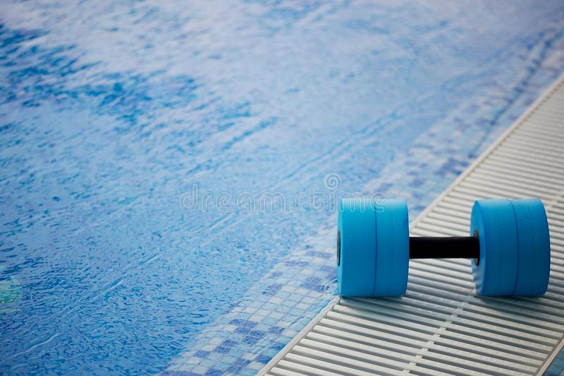 水上体操的kettlebell说谎在水池边缘 在水附近 锻炼,游泳和健康 免版税库存照片