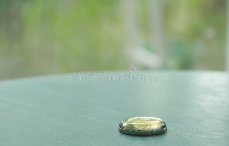 水上面下落在泰国硬币的 免版税库存照片