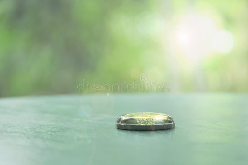 水上面下落在泰国硬币的 图库摄影