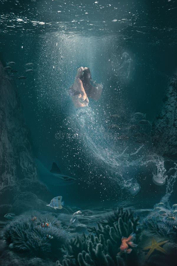 水下的幻想场面半妇女半水母游泳对表面 免版税库存照片