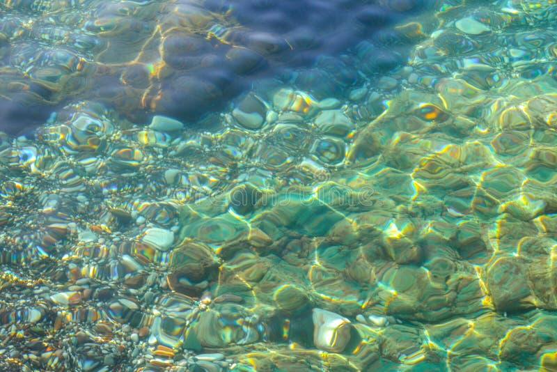 水下的海石头、表面与波纹和波浪,美好的样式透明清楚的水 库存图片
