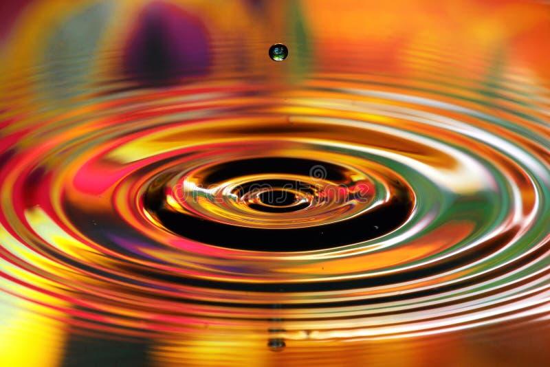 水下落飞溅 红色和黄色波纹,表面上的反射 库存照片