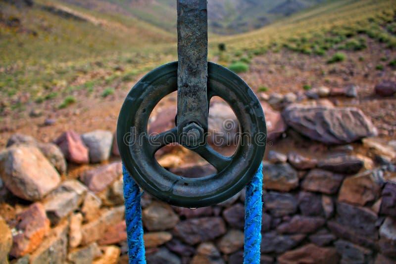 水井老传统与绳索和滑轮接近扎克尔,瓦尔扎扎特,南摩洛哥小的村庄  免版税库存图片