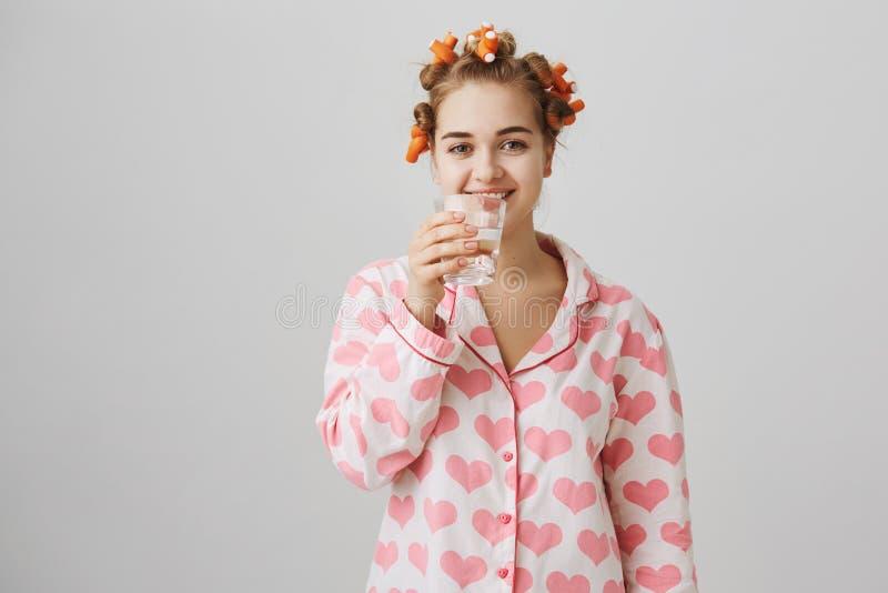 水使您美丽 可爱的白种人女孩室内射击卷发夹和睡衣的有心脏模板的 免版税库存图片