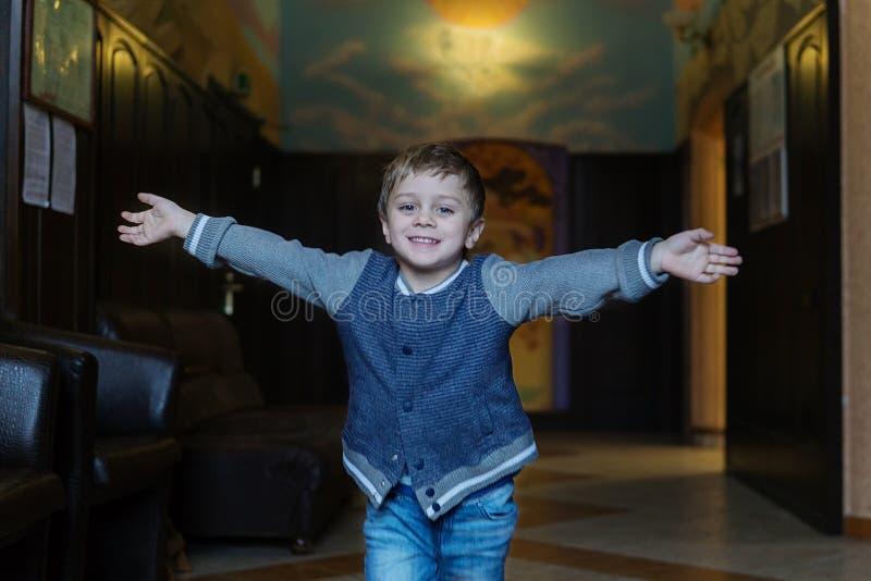 水兵和牛仔裤的一个五岁的男孩在一间快乐的屋子跑在一辛苦的工作和集会以后遇见他的母亲 免版税库存照片