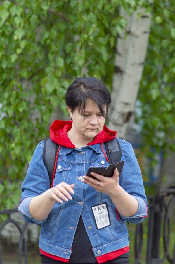 水兵和红色毛线衣的女孩在树背景调查她的智能手机 库存图片