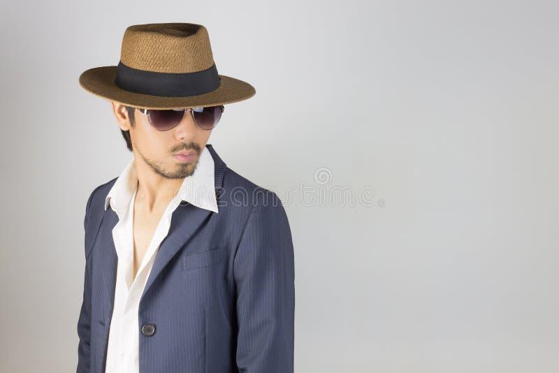水军蓝色衣服的画象人和白色衬衫和帽子和玻璃转动姿势 免版税库存照片