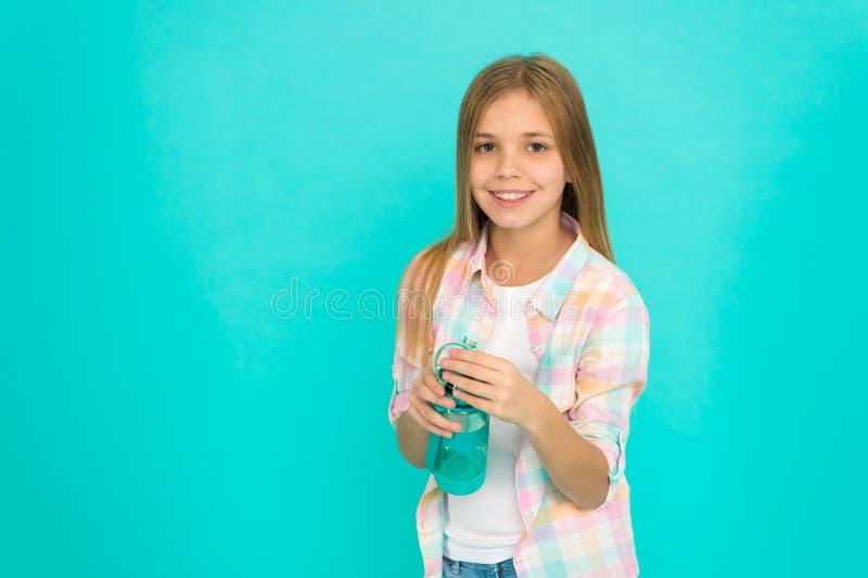 水分平衡小儿科混乱  关于健康和水分平衡的女孩关心 孩子举行瓶蓝色背景 孩子 库存照片