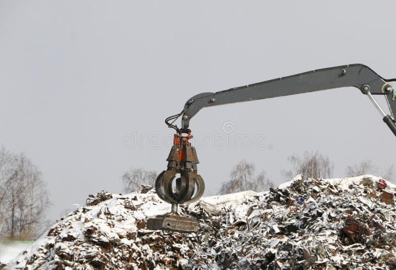 水力劫掠清洗和tampens金属残骸 挖掘机举并且投掷与一个气动力学的爪子的装载有爪的 库存图片